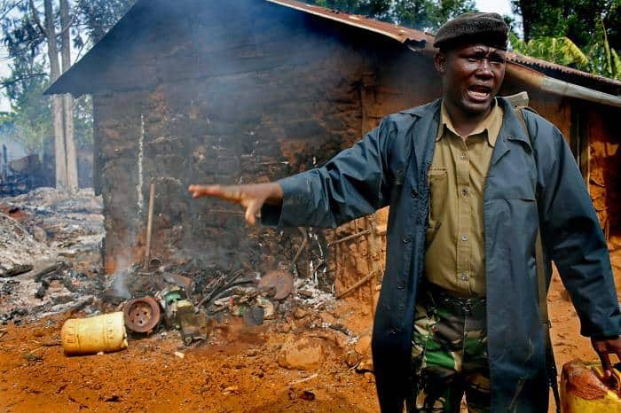 A policeman shouts orders upon arrival at a house that has been torched by Kalinjen men. Kate Holt.