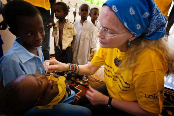 Mia Farrow, UNICEF Goodwill Ambassador, administers polio drops to a young baby in Ndjamena. Kate Holt.