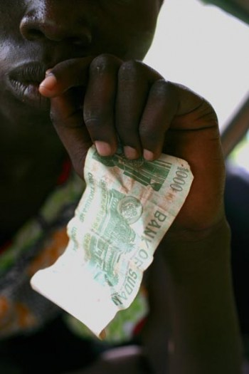 A young girl in Juba who lives on the street holds up the money she made the night before. Kate Holt.