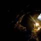 Miners walk along a damp tunnel with a kerosene lamp in an Emerald mine in Khenj. Kate Holt.