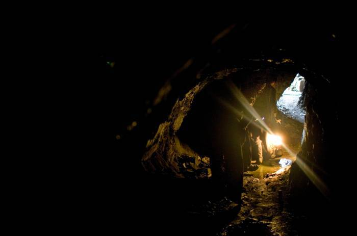 Miners walk along a damp tunnel with a kerosene lamp in an Emerald mine in Khenj. Kate Holt.