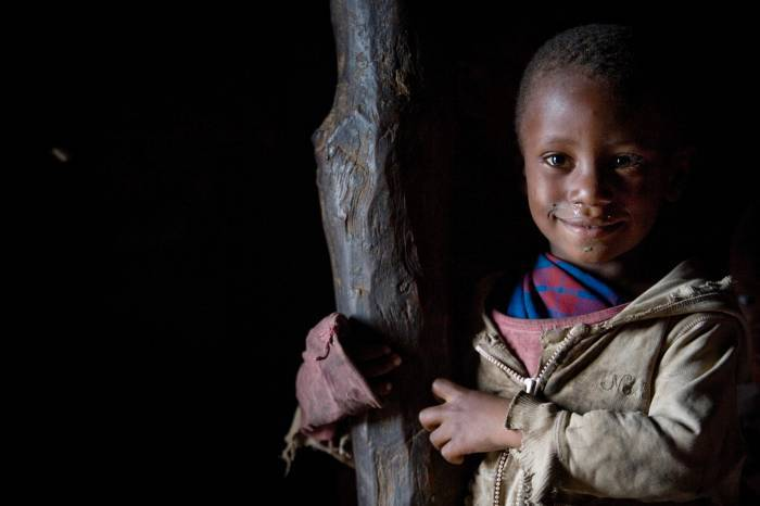 Baby Larumba, who is now attending school regularly, poses for photographs on her homestead. Kate Holt.