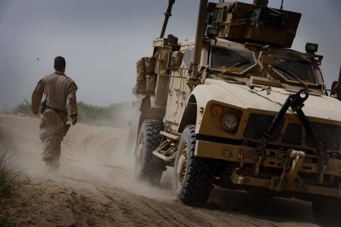 A US Marine walks passed an MRAP armoured vehicle at Forward Operating Base Delhi. Kate Holt.