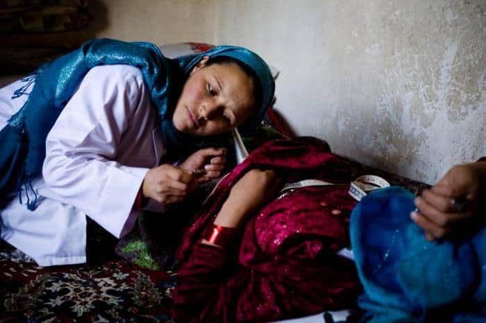 Community midwife, Sadiqa Hosseini, examines a woman who is pregnant in her home. Kate Holt.