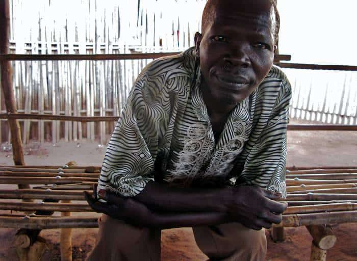 Edward Oboma sits on a bench that he has just built from bamboo, in Custom Market. Kate Holt.