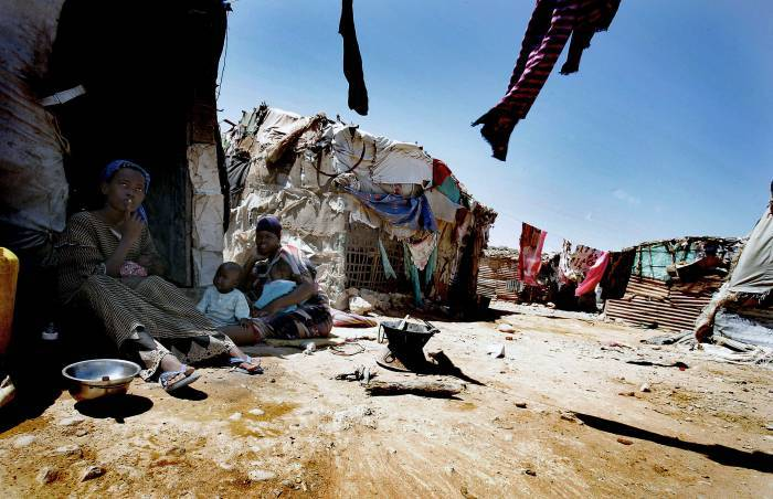 Women and their children sit outside a makeshift shelter in Bosasso, Somalia. Kate Holt.