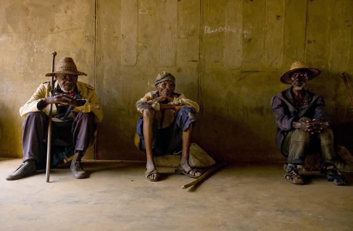 Sekwerekwe Bitoni ( C ) is photographed with two other men at a community meeting. Kate Holt.