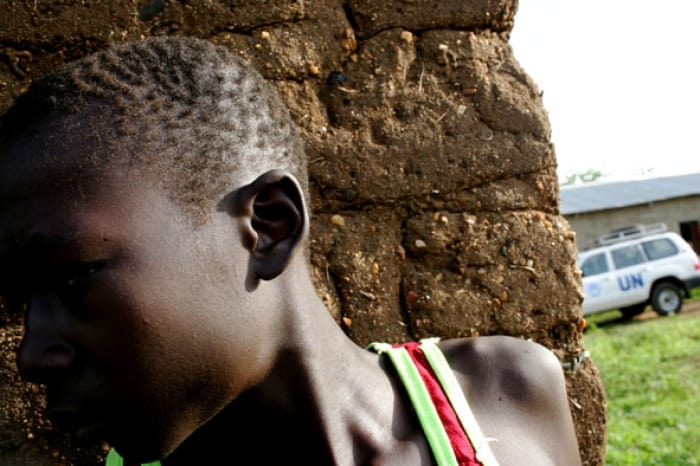 A young boy stands in a doorway in a market place in Juba, with a UN car behind. Kate Holt.