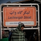 A man walks passed a street sign of Lashkar Gah, in Lashkar Gah, Helmand, Afghanistan. Kate Holt.