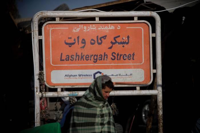 A man walks passed a street sign of Lashkar Gah, in Lashkar Gah, Helmand, Afghanistan. Kate Holt.
