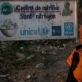 """A young boy stands in front of a sign indicating how many NGO""""s had worked in the camp he is still living in. Kate Holt."""
