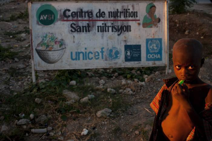 "A young boy stands in front of a sign indicating how many NGO""s had worked in the camp he is still living in. Kate Holt."