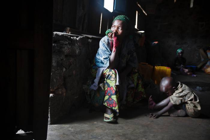 A woman recently displaced by fighting poses for a photograph in a school in Nzumu. Kate Holt.