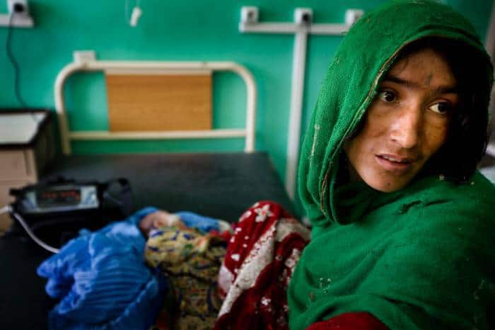 A woman sits with her child who was suffering from severe diarreah in the paediatric unit of Mirwais Hospital. Kate Holt.