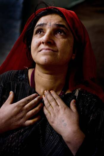Sakina, a 30 year old woman who has six children whom she has to support cries as she tells her story. Kate Holt.