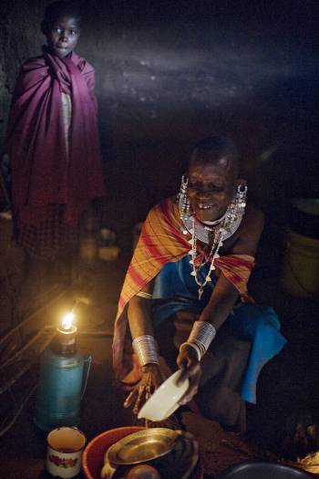 Namayani Ngoliyo stands behind her stepmother Ngaisi who is cooking at her father's house. Kate Holt.