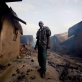 A man stands by the remains of his burnt out home after intense rioting raged through Nakuru. Kate Holt.