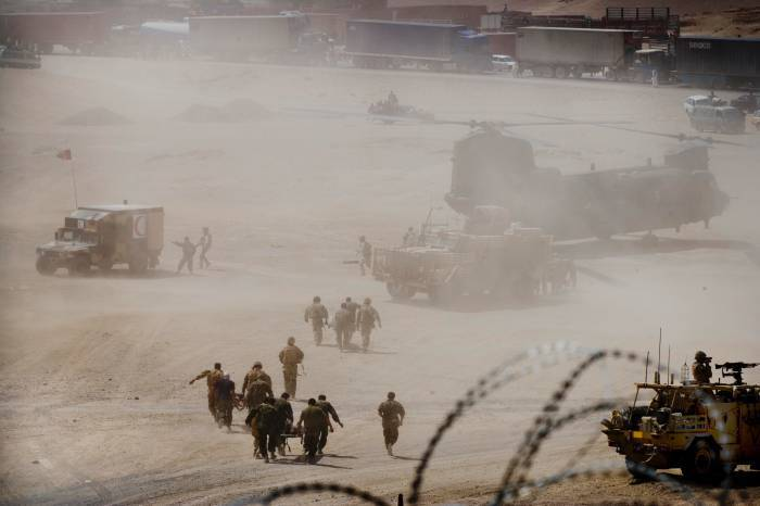 Soldiers from 1 Scots Guards and the Afghan National Army (ANA) run with stretchers. Kate Holt.