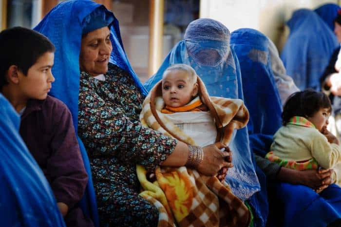 An elderly woman holds her grandchild while she queues to see a doctor at a maternal health clinic. Kate Holt.