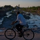 A man cycles passed a river that is heavily polluted and runs passed a camp for displaced people in Port au Prince. Kate Holt.