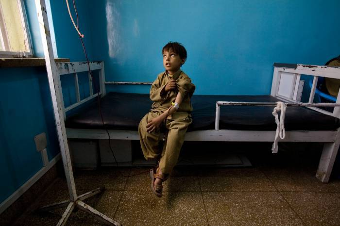 Noman, 7 years old, and who suffers from the rare blood disease, Thalassemia, patiently waits while he has a blood transfusipn. Kate Holt.