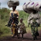 Women walk along a road with their belongings on their heads, near the town of Kibati. Kate Holt.