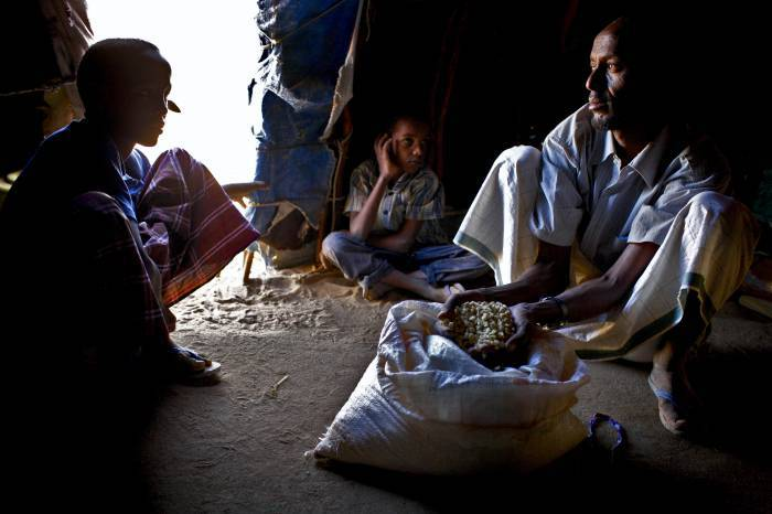 A father with his family shows what remains of their food ration for the month. Kate Holt.