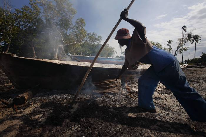 A fisherman burns the bottom of a dugout canoe made from Mango tree, to kill off bugs, in Gazi Bay. Kate Holt.