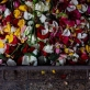 Flowers that have adorned a coffin are left next to a funeral pyre at the funeral of Malti Vaya. Kate Holt.