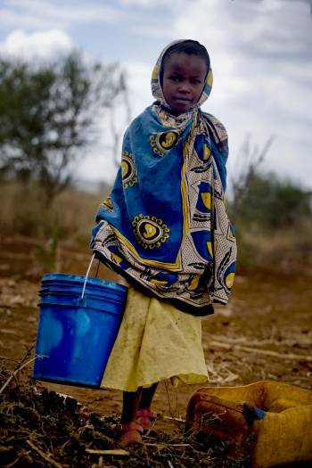 Maua Juma carries water to her family's home from the well in the town of Makuyuni. Kate Holt.