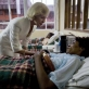 Quentin Bryce, AC, Governor General of Australia, talks to a patient in the female ward of the University Teaching Hospital. Kate Holt.