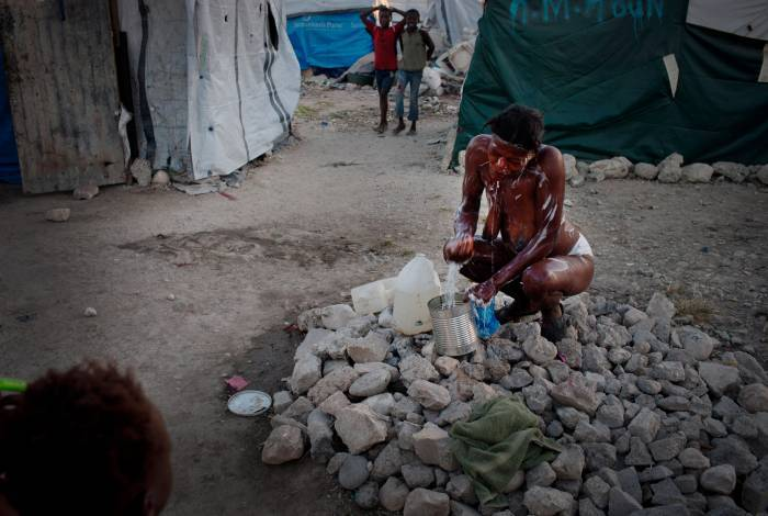 A woman tries to wash herself with no privacy in a camp in Port au Prince. Kate Holt.