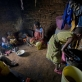 Maua Juma washes the dishes while her mother, Chiku, cooks for the family. Kate Holt.