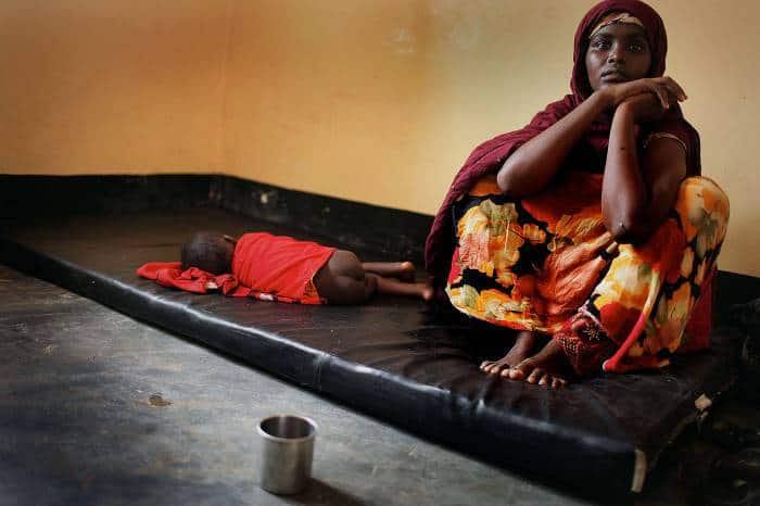 A woman sits next to her son who is suffering from acute dysentery in hospital in South Galkayo, Somalia. Kate Holt.