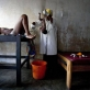A nurse delivers Chance's baby over a bucket in a poorly equipped health center. Kate Holt.