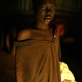 A street boy photographed in the headlights of a passing car in a marketplace where he lives in Juba. Kate Holt.