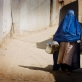 A woman wearing a burka walks down the street carrying cooking pots in District 6 of Kabul. Kate Holt.