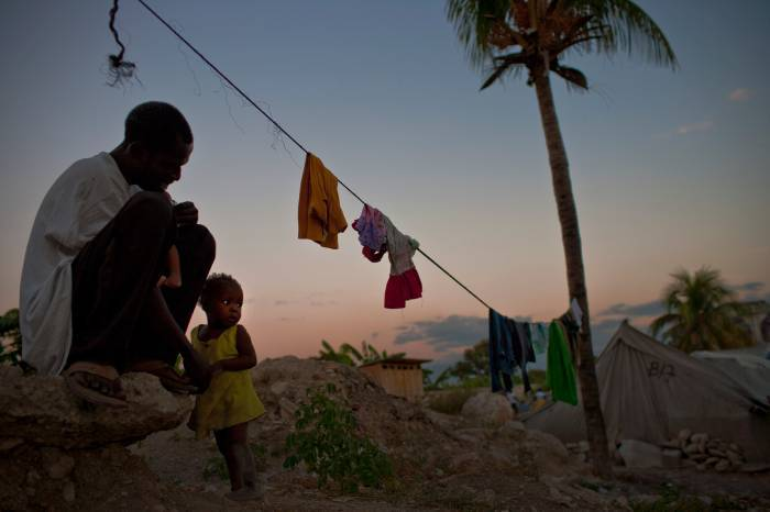 A man holds his daughter while still living in camps in Port au Prince, Haiti on the 17th January, 2013. Kate Holt.