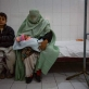 A woman, covered in a Burqa, holds her daughter while waiting to see a doctor. Kate Holt.