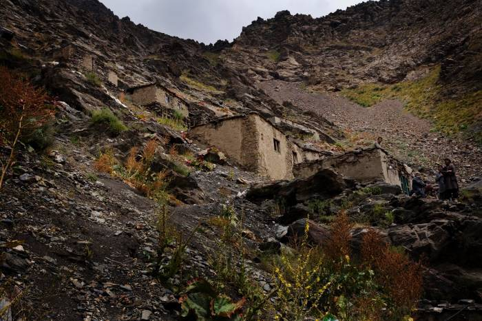 Rough shelters made of local stone perch high up on the side of a mountain. Kate Holt.