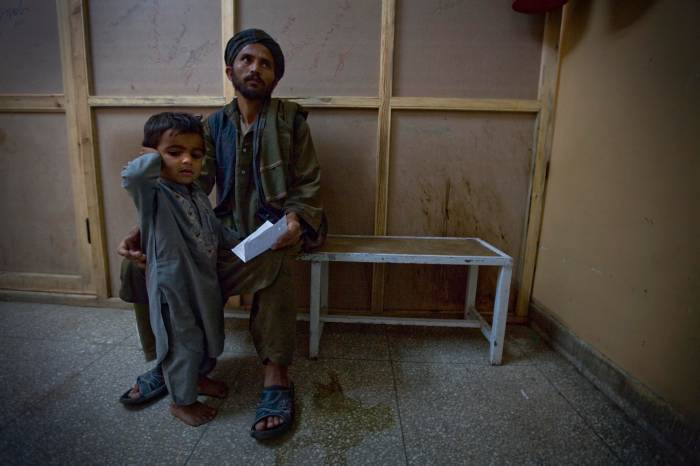 A man waits with his son in the waiting room for paediatric cases in Mirwais Hospital. Kate Holt.