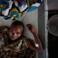 A young girl, suffering from cholera lies on her bed in a cholera treatment centre run by MSF. Kate Holt.