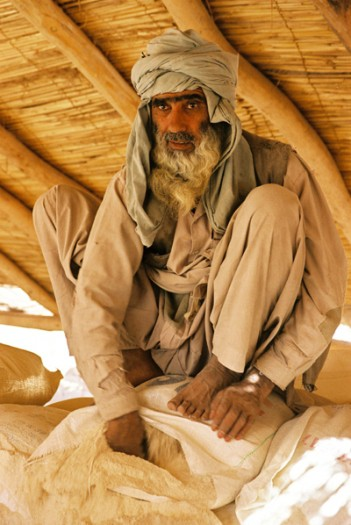 A man sits on a flour sack at a food distribution point for refugees. Kate Holt.