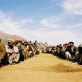 A group of men await allocation of a tent and non food items after crossing the border. Kate Holt.