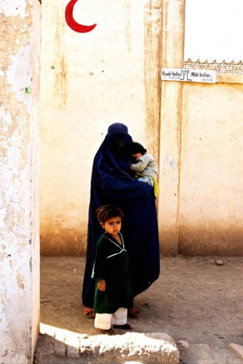 A widow from Afghanistan waits for help outside a medical center in a refugee camp in Pakistan. Kate Holt.