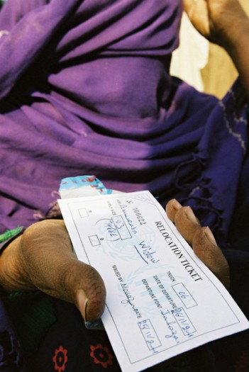 A widow from Afghanistan holds out her identity card stating that she is a widow. Kate Holt.