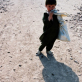 A young boy carries part of his family's food ration to their home in a refugee settlement. Kate Holt.
