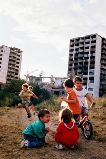 Children play outside of a bombed apartment block in Sarajevo. Kate Holt.