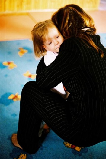 A young child at an orphanage in Bosnia Herzegovina receives a hug from a care worker. Kate Holt.