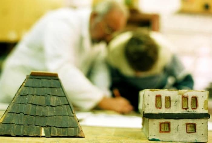 A boy, abandoned by his mother during the war, is seen here building a model house. Kate Holt.